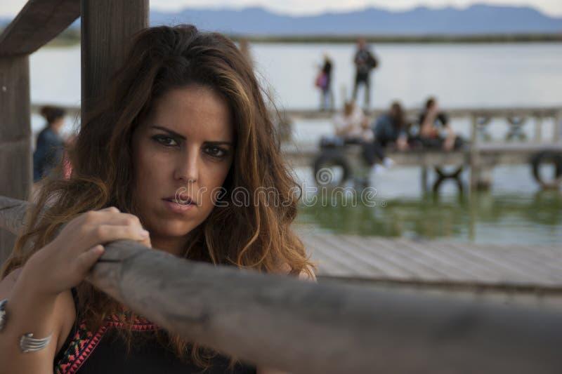 Jeune femme posant regardant la caméra se reposant à côté d'une balustrade en bois photo stock