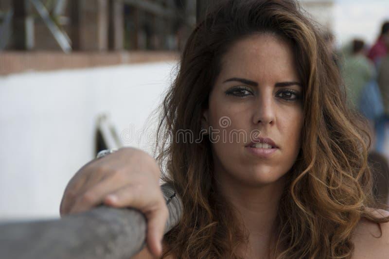 Jeune femme posant regardant la caméra se reposant à côté d'une balustrade en bois images libres de droits
