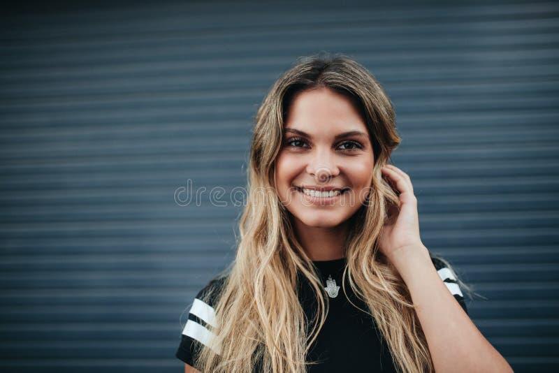 Jeune femme posant sur le fond gris photos stock