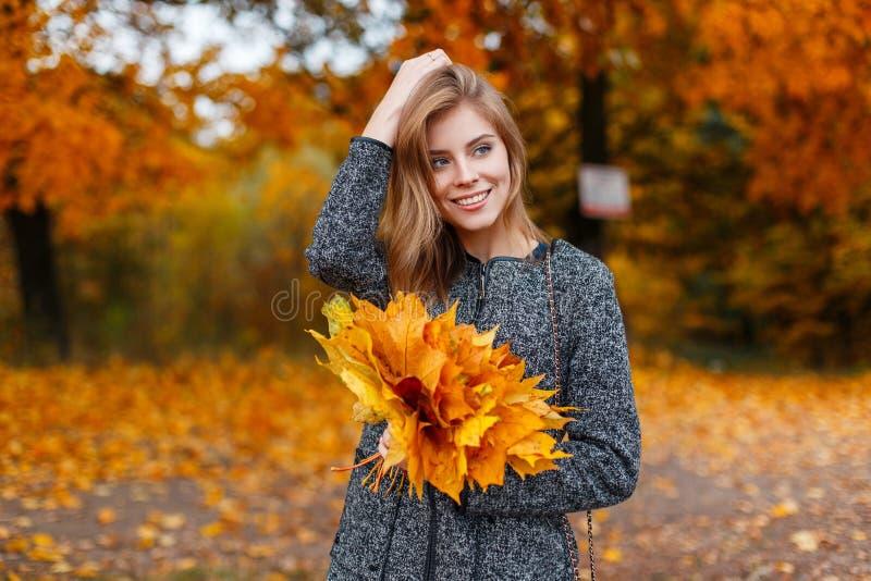 Jeune jeune femme positive avec un beau sourire dans un manteau gris à la mode avec un bouquet des feuilles de jaune-or d'automne image stock