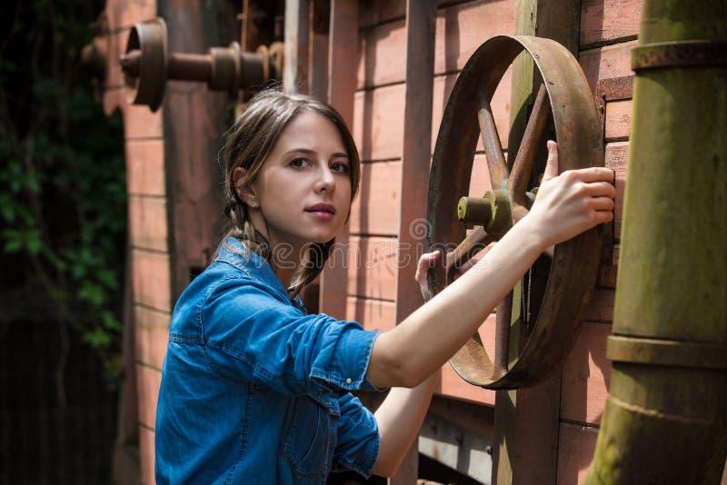 Jeune femme près de roue d'une vieille moissonneuse de cartel en bois XIX de siècle photographie stock libre de droits