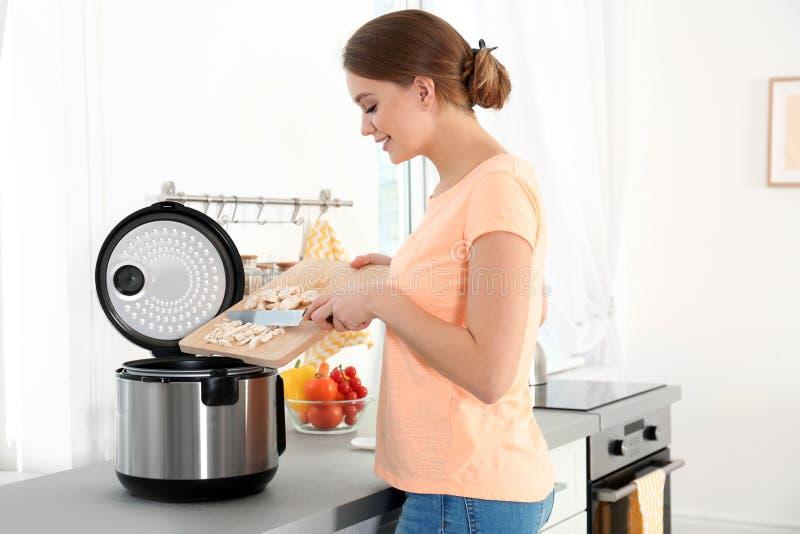 Jeune femme préparant des champignons avec le cuiseur multi moderne image libre de droits