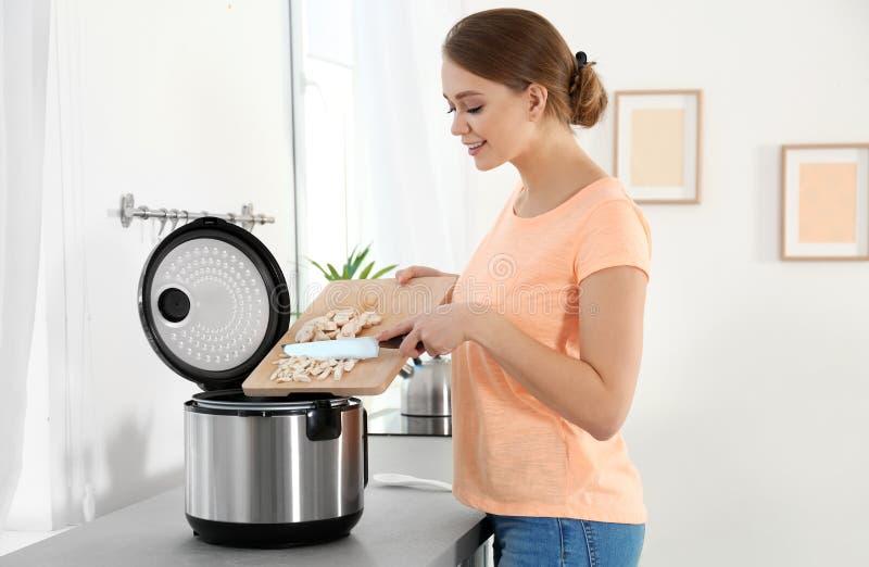Jeune femme préparant des champignons avec le cuiseur multi moderne image stock