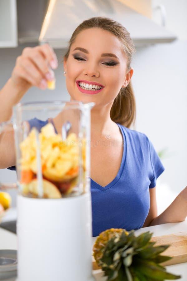 Jeune femme préparant la boisson avec l'ananas photographie stock libre de droits