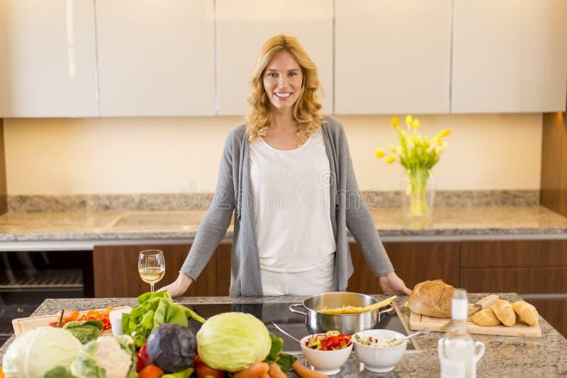 Jeune femme préparant la nourriture dans la cuisine moderne images stock