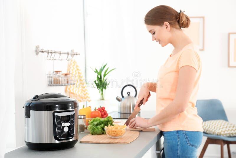 Jeune femme préparant la nourriture près du cuiseur multi moderne photo stock