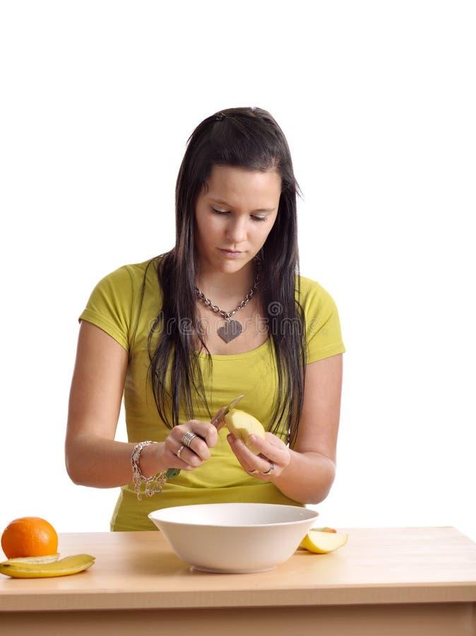 Jeune femme préparant une salade de fruits image libre de droits