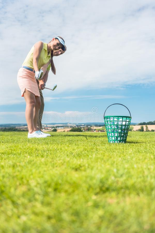 Jeune femme pratiquant le mouvement correct pendant la classe de golf avec photo libre de droits