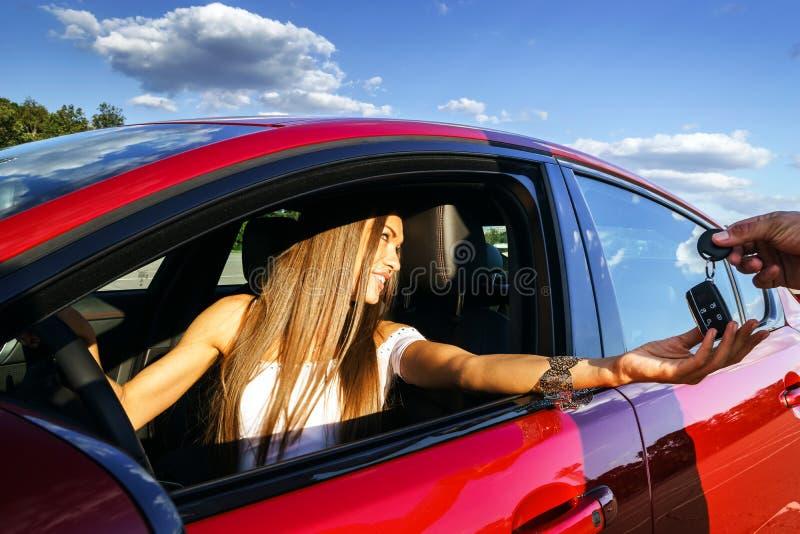 Jeune femme prenant des clés de nouvelle voiture photo libre de droits