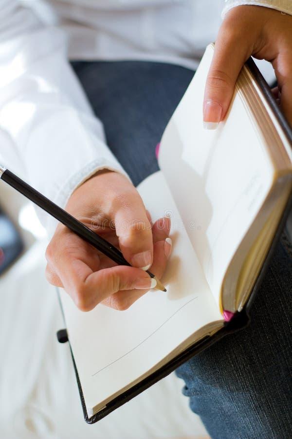 Jeune femme prenant des notes photo stock