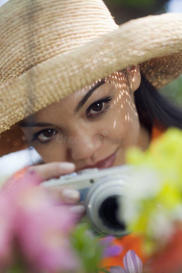 Jeune femme prenant des photos des fleurs photos libres de droits
