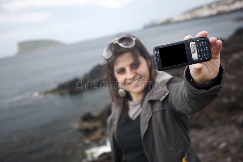 Jeune femme prenant l'autoportrait avec le téléphone portable photographie stock