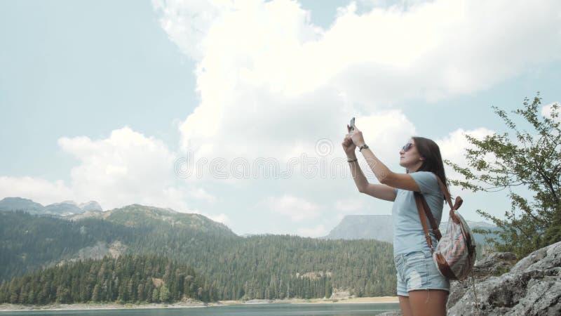 Jeune femme prenant la photo par Smartphone devant le lac mountain Belle fille caucasienne passant le temps dans un Moutain images stock