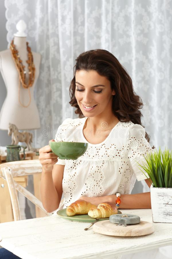 Jeune femme prenant le petit déjeuner à la maison images libres de droits