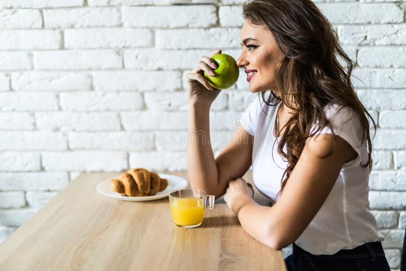 Jeune femme prenant le petit déjeuner à la maison, mangeant de la nourriture saine images libres de droits