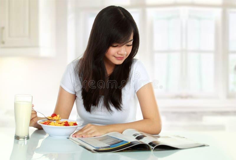 Jeune femme prenant le petit déjeuner images libres de droits