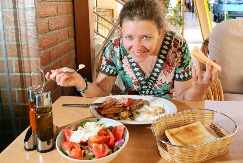 Jeune femme prenant le petit déjeuner image libre de droits