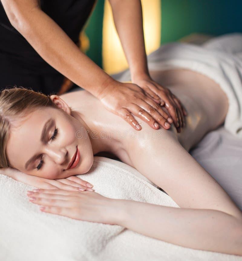 Jeune femme prenant le plaisir sur le lit de massage, avec des yeux fermés Femme Salon de station thermale images stock