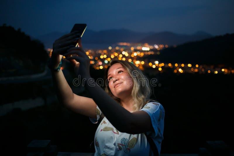 Jeune femme prenant le selfie sur la colline observant la vue de ville de nuit Bonne lumière d'écran image libre de droits