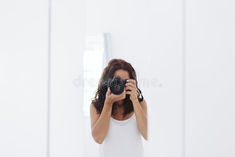 Jeune femme prenant un autoportrait dans le miroir ? la maison Murs et fond blancs Cam?ra r?flexe couvrant son visage lifestyle images stock
