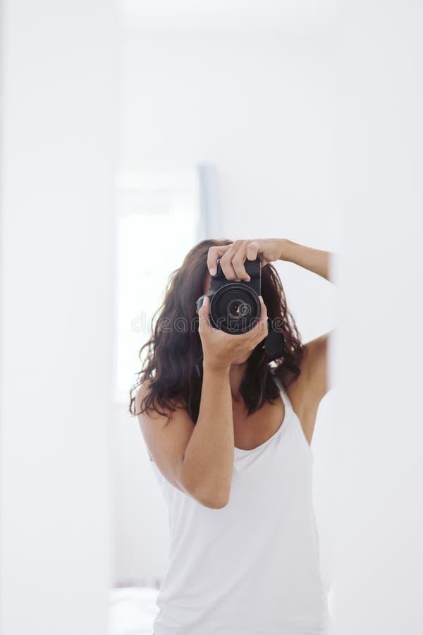 Jeune femme prenant un autoportrait dans le miroir ? la maison Murs et fond blancs Cam?ra r?flexe couvrant son visage lifestyle photographie stock libre de droits