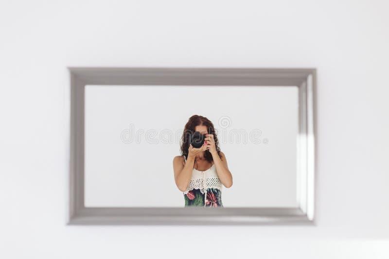 Jeune femme prenant un autoportrait dans le miroir ? la maison Murs et fond blancs Cam?ra r?flexe couvrant son visage lifestyle photo libre de droits