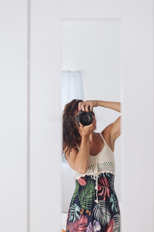 Jeune femme prenant un autoportrait dans le miroir ? la maison Murs et fond blancs Cam?ra r?flexe couvrant son visage lifestyle photographie stock