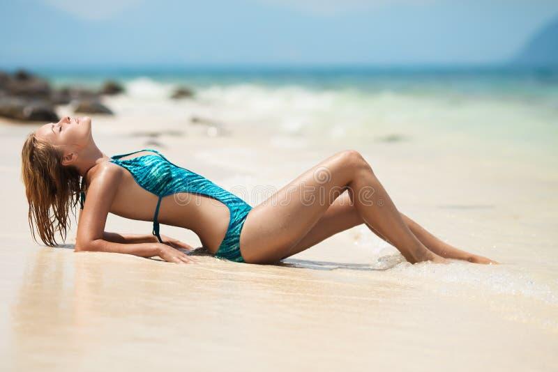 Jeune femme prenant un bain de soleil à la plage tropicale photographie stock