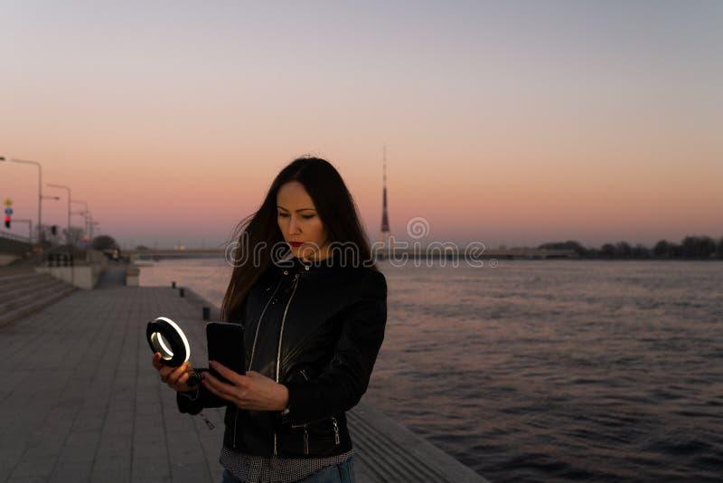 Jeune femme prenant un selfie utilisant un éclair d'anneau comme lumière de suffisance à un coucher du soleil avec une vue au- photo stock