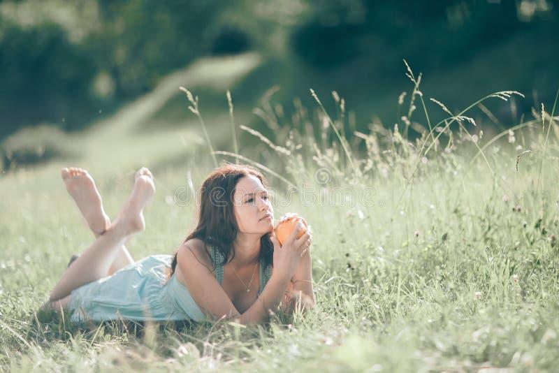 Jeune femme réfléchie avec la détente orange sur la pelouse photographie stock libre de droits