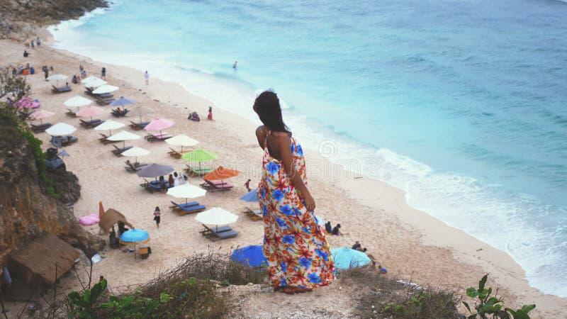 Jeune femme réfléchie de brune dans la longue robe se tenant sur une roche à côté de l'océan image libre de droits