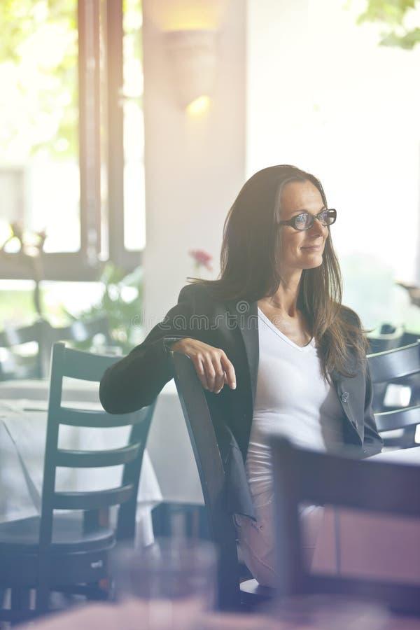 Jeune femme réfléchie et jolie s'asseyant dans un restaurant image libre de droits