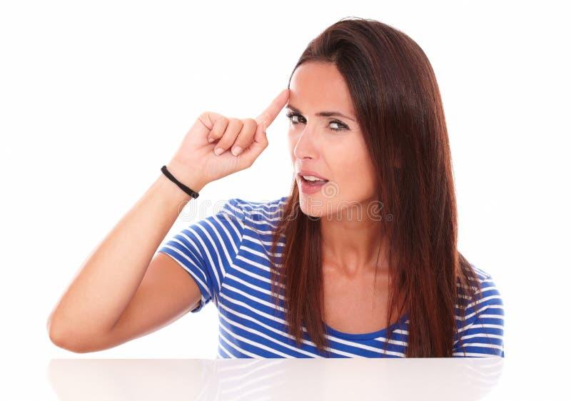 Jeune femme réfléchie indiquant son front photographie stock