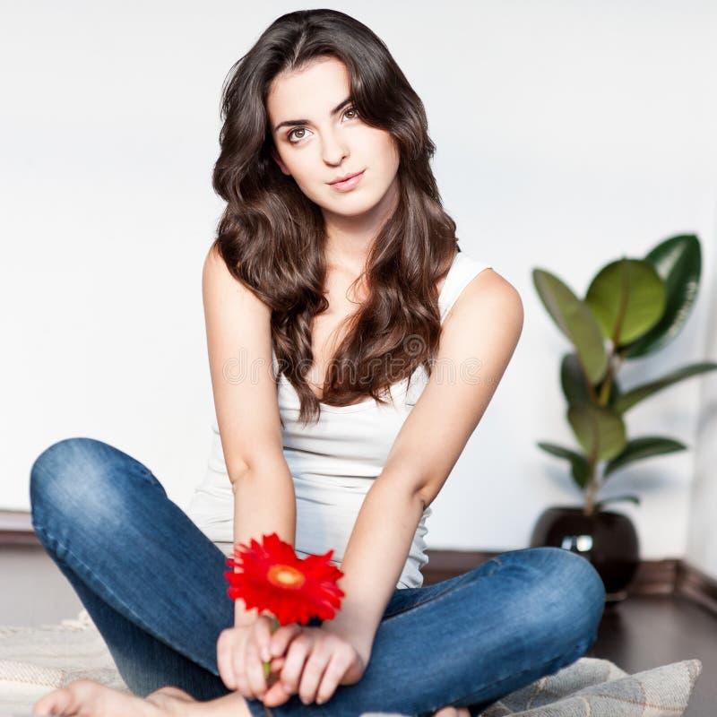 Jeune femme réfléchie s'asseyant avec la fleur rouge photo stock