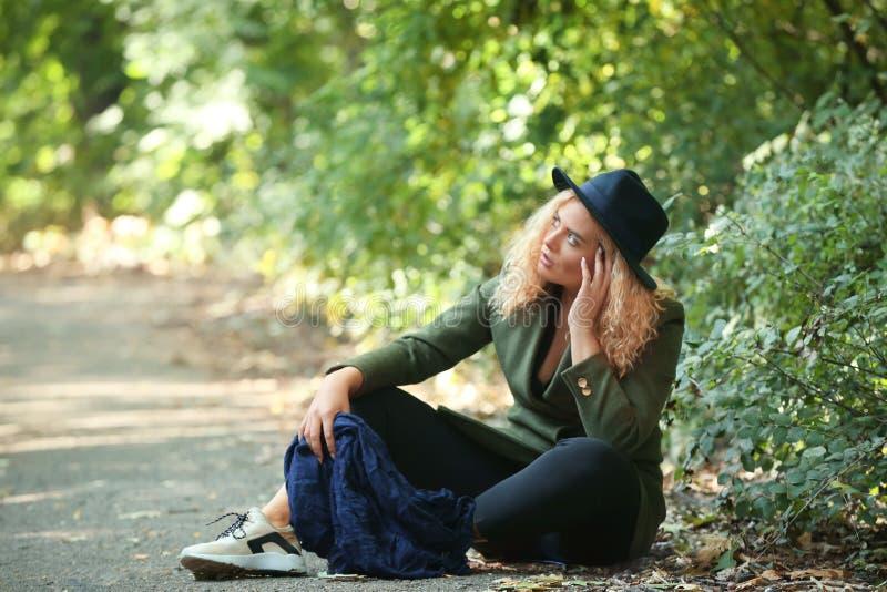 Jeune femme réfléchie s'asseyant sur la terre en parc image libre de droits