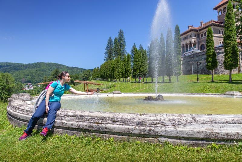 Jeune femme régénérant dans la fontaine devant le château de Cantacuzino dans Busteni, Roumanie photos libres de droits