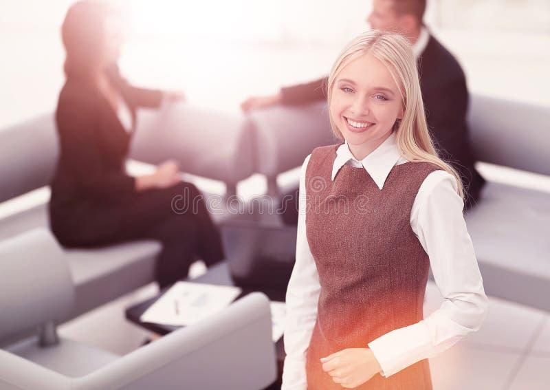 Jeune femme réussie d'affaires sur le bureau brouillé de fond photographie stock