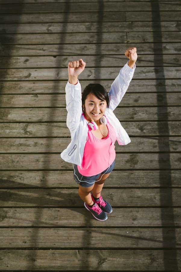 Jeune femme réussie sportive soulevant des bras images stock