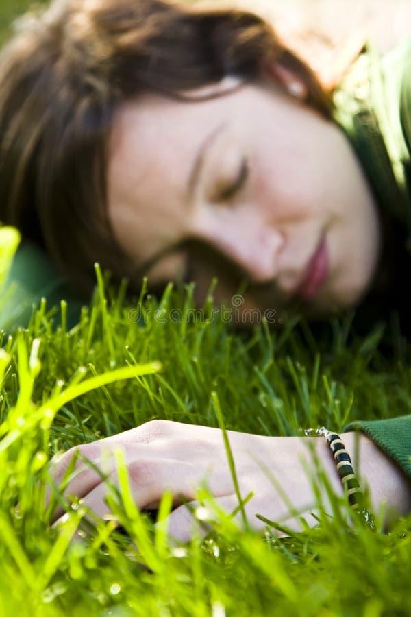 Jeune femme rêvant dans l'herbe image stock