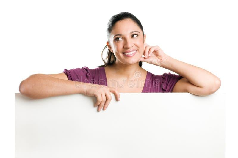 Jeune femme rêvant retenant le panneau indicateur blanc photo libre de droits