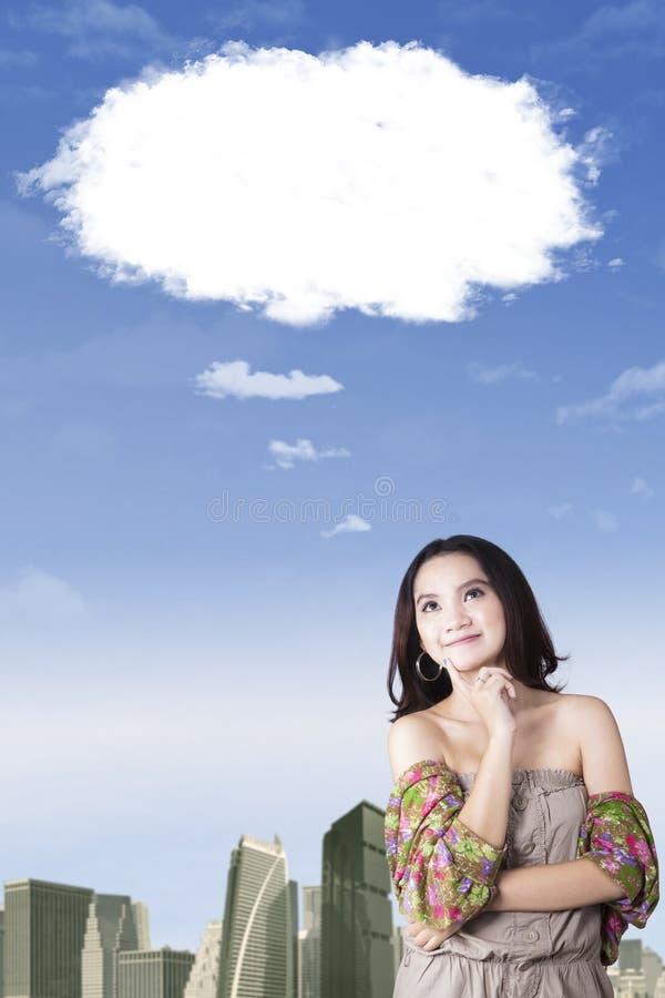 Jeune femme rêvassant avec le nuage de bulle photographie stock