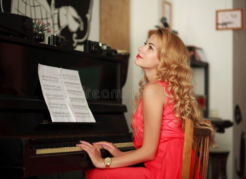 Jeune femme rêveuse s'asseyant au piano dans la chambre images stock