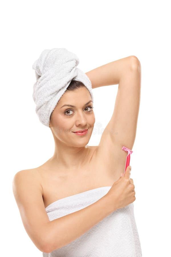 Jeune femme rasant son aisselle avec un rasoir image libre de droits