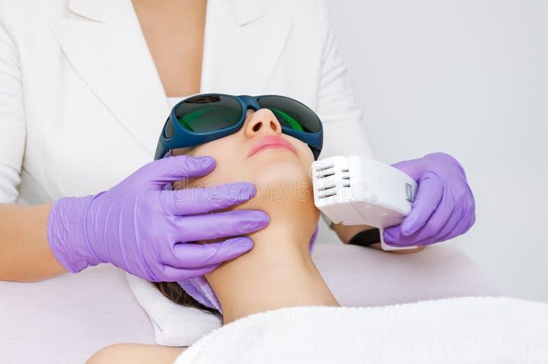 Jeune femme recevant le traitement de laser d'epilation photos libres de droits