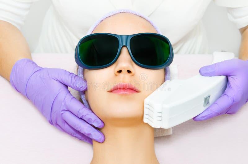 Jeune femme recevant le traitement de laser d'epilation image stock