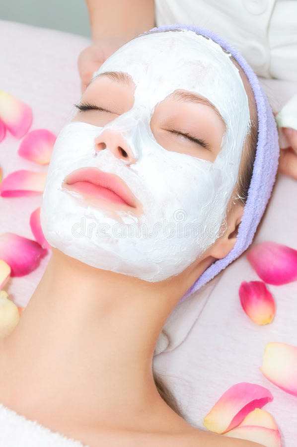 Jeune femme recevant le traitement facial photos stock