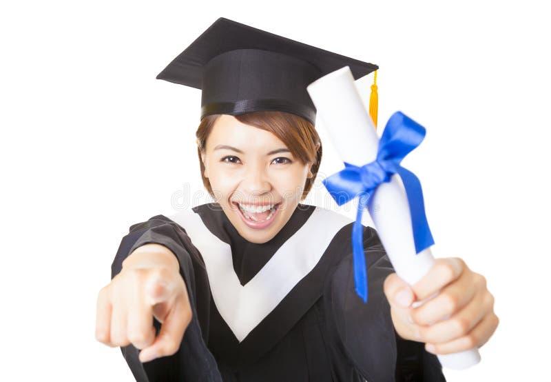 Jeune femme recevant un diplôme et indiquant l'appareil-photo image libre de droits