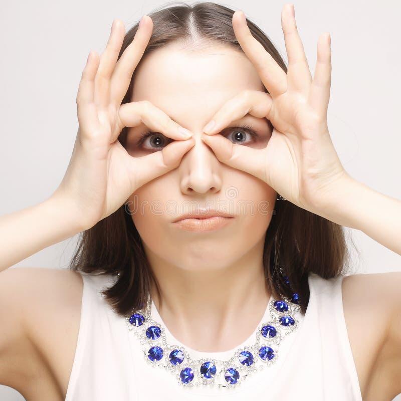 Jeune femme recherchant quelque chose avec les yeux grands ouverts et binoculaire imaginaire photo stock