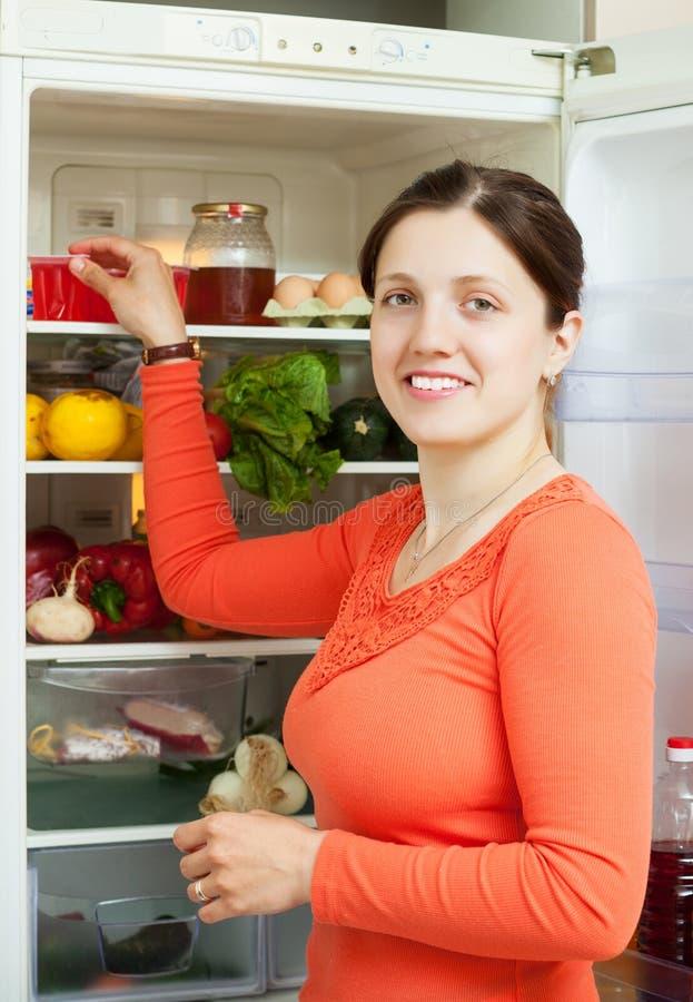 Jeune femme recherchant quelque chose dans le réfrigérateur photos stock