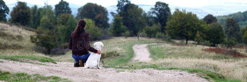 Jeune femme regardant dans l'horizon avec le chiot image stock